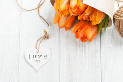 Frühlingsgrußkarte mit orange Tulpen, hölzernes Herz Stockbilder