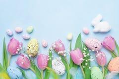 Frühlingshintergrund mit Blumen, Häschen, bunten Eiern und Federn auf blauer Tischplatteansicht Glückliche Ostern-Karte Stockbild