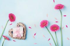 Frühlingshintergrund mit Blumen, Herzen und Geschenkbox auf blauer Tischplatteansicht Grußkarte für Geburtstags-, Frauen-oder Mut Lizenzfreies Stockbild
