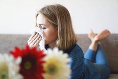 Frühlingskälte oder -allergien Attraktives Mädchen ist zu den Blumen, benutzt eine Serviette allergisch stockbilder