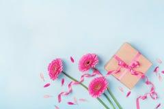 Frühlingskarte für Geburtstags-, Frauen-oder Mutter-Tag Rosa Blumen und Geschenkbox auf blauer Tischplatteansicht flache Lageart Stockfotos