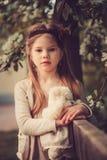 Frühlingslandporträt des entzückenden träumerischen Kindermädchens nahe Bretterzaun mit Teddybären Lizenzfreies Stockfoto