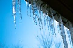 Frühlingslandschaft mit den Eiseiszapfen, die vom Dach des Hauses hängen Stockbilder
