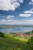 Frühlingslandschaft mit Dorf, See, blauem Himmel und Wolken Stockbild