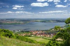 Frühlingslandschaft mit Dorf, See, blauem Himmel und Wolken Stockfotos