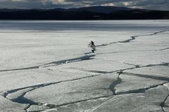 Frühlingslandschaft mit Eisgang auf dem See und ein Radfahrer, der auf ihn fährt stockfotografie
