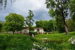 Frühlingslandschaft mit Pavillonruinen, -teich und -wasserfall Park Oleksandriya in Bila Tserkva, Ukraine Stockfoto