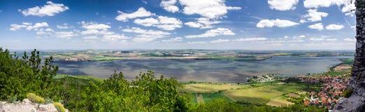 Frühlingslandschaft mit See, Dorf und blauem Himmel mit Wolken Lizenzfreie Stockbilder