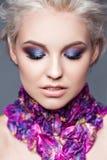 Frühlingsmädchen mit modischem bilden rauchige Augen Schließen Sie erklärte Haare, mit den violetten Blumenblättern einer Tulpe a Lizenzfreie Stockfotografie