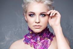 Frühlingsmädchen mit modischem bilden rauchige Augen Schließen Sie erklärte Haare, mit den violetten Blumenblättern einer Tulpe a Stockfoto