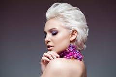 Frühlingsmädchen mit modischem bilden rauchige Augen Schließen Sie erklärte Haare, mit violettem petalsof eine Tulpe auf ihrem Ha Stockfotos