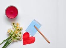 Frühlingsnarzissen bouqet auf dem weißen Hintergrund mit rotem Papier Lizenzfreies Stockfoto