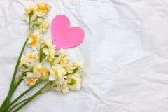 Frühlingsnarzissen bouqet auf dem weißen Kraftpapierhintergrund mit Stockfoto
