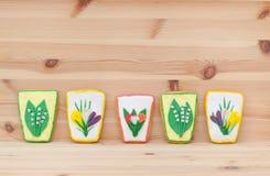 Frühlingsostern-Lebkuchen mit Blumen auf dem hölzernen Hintergrund Lizenzfreies Stockbild