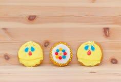 Frühlingsostern-Lebkuchen mit Lächelngesicht auf dem Holz Lizenzfreie Stockfotos