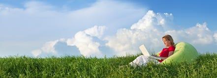 Frühlingspanorama mit der Frau, die draußen sitzt lizenzfreie stockfotos