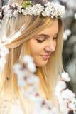 Frühlingsporträt der Frau unter blühenden Niederlassungen Stockfoto