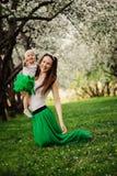 Frühlingsporträt des Mutter- und Babytochterspielens im Freien in zusammenpassender Ausstattung - lange Röcke und Hemden stockfotografie
