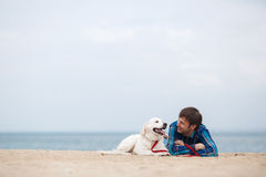 Frühlingsporträt eines jungen Mannes mit einem Hund auf dem Strand Lizenzfreie Stockfotografie