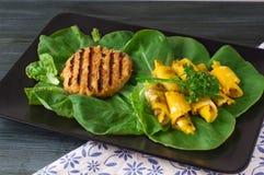 Frühlingsrollen mit Fleischkotelett auf einer Platte mit Grüns Lizenzfreies Stockfoto