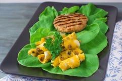 Frühlingsrollen mit Fleischkotelett auf einer Platte mit Grüns Lizenzfreie Stockfotografie