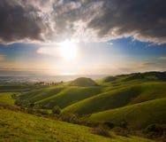 Frühlingssonnenuntergang über grünen Hügeln Lizenzfreies Stockfoto