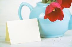 Frühlingstulpenblumenstrauß in der Teekanne über hölzernem Hintergrund Lizenzfreies Stockfoto