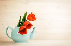 Frühlingstulpenblumenstrauß in der Teekanne über hölzernem Hintergrund Lizenzfreie Stockfotos