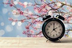 Frühlingszeitumstellungskonzept mit Wecker auf Holztisch über Naturbaumblüte Stockfoto