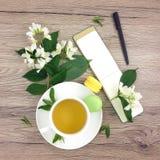 Frühlingszusammensetzung der Tasse Tee, Notizbuch und Blumen auf Holztisch, flache Lage Stockfotografie
