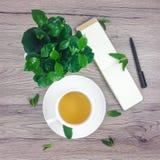 Frühlingszusammensetzung der Tasse Tee, Notizbuch- und Kaffeeanlage des umweltgerechten Hauses auf Holztisch, flache Lage Lizenzfreie Stockbilder