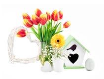 Frühlingszusammensetzung mit Blumen, Nistkasten, Ei und Herzen, ISO Stockbild