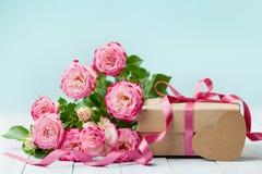 Frühlingszusammensetzung mit rosa Blumen stieg und Geschenkbox auf Weinlesetabelle Grußkarte für Geburtstags-, Frauen-oder Mutter Lizenzfreies Stockbild