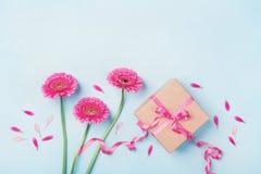 Frühlingszusammensetzung mit rosa Blumen und Geschenkbox auf blauer Tischplatteansicht Grußkarte für Geburtstags-, Frauen-oder Mu Stockbild