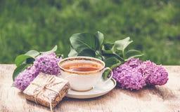 Frühlingszusammensetzung mit Tasse Tee und Flieder Tasse Tee und Niederlassung der Flieder Romantisches Konzept Stockfotografie