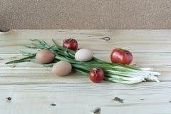 Frühlingszwiebeln mit roten Tomaten und Hühnereien auf einem hölzernen surfac Lizenzfreies Stockfoto
