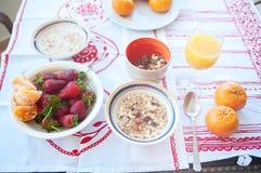 Frühstück auf dem Tisch, Saft, Getreide und Früchte in der Sonne goo lizenzfreie stockbilder