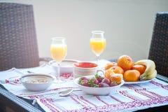 Frühstück auf dem Tisch, Saft, Getreide und Früchte in der Sonne goo stockbilder