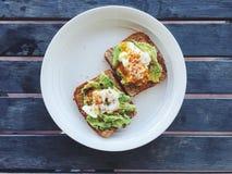 Frühstück: Avocadotoast mit poschiertem Ei und Paprika blättert ab Lizenzfreie Stockfotografie