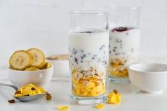 Frühstück in der Glasschale: selbst gemachtes Granola, Banane, frische Beeren, Jogurt auf weißem Hintergrund Das Konzept der gesu Lizenzfreie Stockbilder