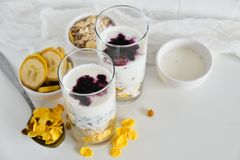 Frühstück in der Glasschale: selbst gemachtes Granola, Banane, frische Beeren, Jogurt auf weißem Hintergrund Das Konzept der gesu Stockfotos