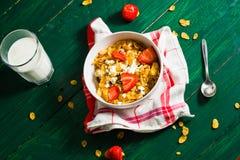 Frühstück des Hafermehls und der Corn Flakes mit Milch und Erdbeeren stockfoto