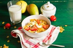 Frühstück des Hafermehls und der Corn Flakes mit Milch und Erdbeeren lizenzfreie stockbilder