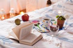 Frühstück diente im Bett mit Tee, Schokolade und Frucht Lizenzfreie Stockbilder