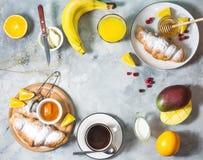 Frühstück diente mit Kaffee, Orangensaft, Hörnchen und Früchten auf konkretem Hintergrund stockbild