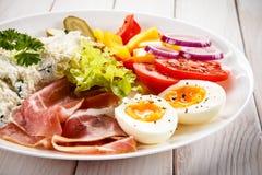 Frühstück - gekochtes Ei, Speck, Hüttenkäse und Gemüse Stockfoto