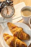 Frühstück-Hörnchen, Kaffee und Alarmuhr Lizenzfreies Stockfoto