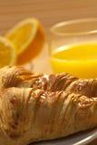 Frühstück-Hörnchen, Orangen und Orangensaft Lizenzfreies Stockfoto