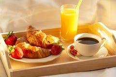 Frühstück im Bett, ein Behälter des Kaffees, Hörnchen, Saft und frische Erdbeeren Fr?her Morgen lizenzfreie stockbilder