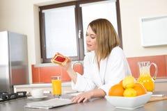 Frühstück - lächelnde Frauenlesezeitung Stockbilder